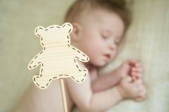 A tabuleta de madeira das crianças contra o bebê de sono Fotografia de Stock Royalty Free