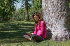 Tabuleta de observação da mulher que senta-se na grama ao lado da árvore Imagens de Stock Royalty Free