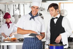 Tabuleta de With Waiter Using Digital do cozinheiro chefe Fotografia de Stock Royalty Free