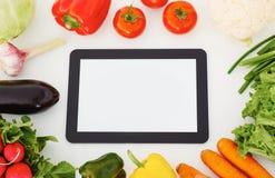 Tabuleta digital do tela táctil, legumes frescos e grama em uma tabela de madeira branca imagem de stock royalty free