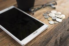 A tabuleta digital do tipo de Asus pôs sobre um fundo de madeira da tabela Fotos de Stock Royalty Free