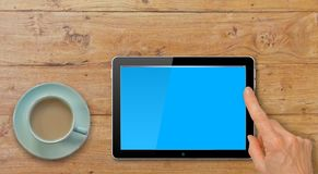 Tabuleta do computador com a mão que aponta ou que Swiping na tabela pelo copo do café ou de chá Imagem de Stock