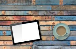 A tabuleta do computador com a tela vazia no azul pintou a tabela pelo copo do café ou de chá Fotografia de Stock Royalty Free