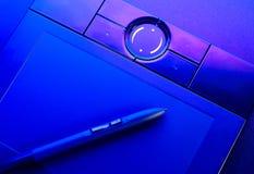 Tabuleta do desenho com a pena na luz azul Imagens de Stock