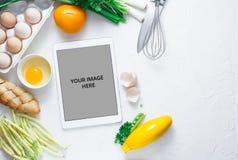 Tabuleta do tela táctil de Digitas com legumes frescos e utensílios da cozinha no fundo, vista superior fotografia de stock royalty free
