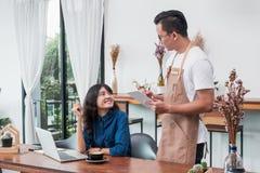 A tabuleta do uso do garçom de Ásia Barista toma a ordem do cliente no coffe Imagem de Stock