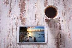 Tabuleta e café preto na tabela de madeira Fotografia de Stock