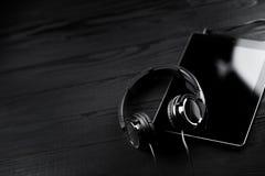 Tabuleta e fones de ouvido de Digitas em uma tabela de madeira escura fotos de stock royalty free