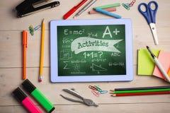 Tabuleta em uma tabela da escola com ícones da escola na tela Imagem de Stock Royalty Free