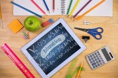 Tabuleta em uma tabela da escola com ícones da escola na tela Imagens de Stock Royalty Free