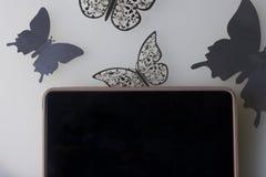 A tabuleta encontra-se em uma superfície branca Em torno dele ornamento das borboletas, corte da folha Fotografia de Stock Royalty Free