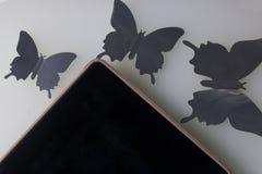 A tabuleta encontra-se em uma superfície branca Em torno dele ornamento das borboletas, corte da folha Imagem de Stock Royalty Free