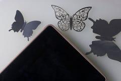 A tabuleta encontra-se em uma superfície branca Em torno dele ornamento das borboletas, corte da folha Imagens de Stock