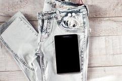 Tabuleta, fones de ouvido, calças de brim Imagens de Stock