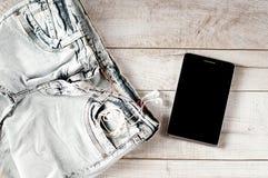 Tabuleta, fones de ouvido, calças de brim dobradas Fotos de Stock