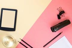 Tabuleta, fontes de escola, caderno e marcadores coloridos no fundo cor-de-rosa e bege pastel foto de stock