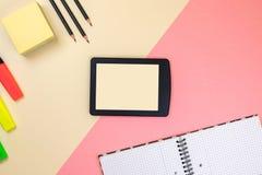 Tabuleta, fontes de escola, caderno e marcadores coloridos no fundo cor-de-rosa e bege pastel fotografia de stock