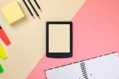 Tabuleta, fontes de escola, caderno e marcadores coloridos no fundo cor-de-rosa e bege pastel foto de stock royalty free