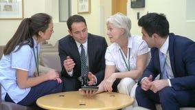Tabuleta médica de Team Discussing Patient Notes On Digital video estoque