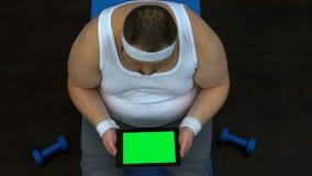 Tabuleta masculina excesso de peso do desdobramento que senta-se na esteira, conselho em linha do perito da dieta filme