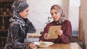 Tabuleta muçulmana bonita do uso da mulher dois no café video estoque