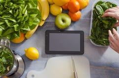Tabuleta no contador de cozinha, espaço da cópia, frutas e legumes ao lado dele Imagem de Stock