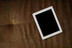 Tabuleta no sofá marrom Imagem de Stock Royalty Free
