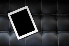 Tabuleta no sofá preto Imagem de Stock
