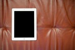 Tabuleta no sofá vermelho Foto de Stock Royalty Free
