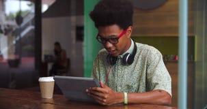 Tabuleta nova de Working On Digital do homem de negócios na cafetaria filme