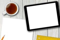 A tabuleta, o copo de chá e o papel digitais vazios cobrem na tabela de madeira Imagens de Stock Royalty Free