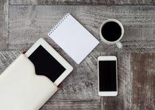 A tabuleta, o telefone, a x?cara de caf? e o caderno brancos est?o na tabela Trabalho em casa freelance imagens de stock royalty free