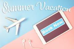 Tabuleta para o livro das férias agora com plano para a agência de viagens imagens de stock royalty free