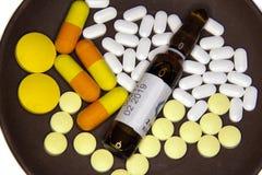 Tabuletas, cápsulas e ampolas com medicina em uma placa Imagens de Stock Royalty Free
