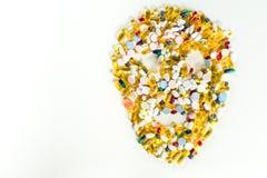 Tabuletas, comprimidos e cápsulas, que dão forma a um crânio assustador no fundo branco com espaço da cópia Fotografia de Stock Royalty Free