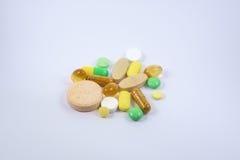 Tabuletas do suplemento ao alimento e medicinas, fundo branco Fotografia de Stock Royalty Free