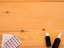 Tabuletas e gotas em um fundo de madeira claro imagens de stock
