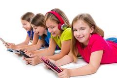 Tabuletas e smatphones da tecnologia das meninas da criança das irmãs Imagem de Stock
