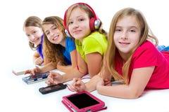 Tabuletas e smatphones da tecnologia das meninas da criança das irmãs Fotos de Stock