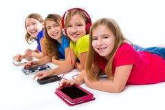 Tabuletas e smatphones da tecnologia das meninas da criança das irmãs Fotografia de Stock Royalty Free