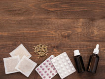 Tabuletas, gotas e herbals em um fundo de madeira escuro foto de stock