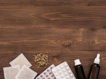 Tabuletas, gotas e herbals em um fundo de madeira escuro fotografia de stock