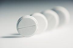 Tabuletas médicas brancas redondas no conceito do cinza, da medicina e dos cuidados médicos Fotografia de Stock