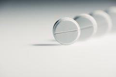 Tabuletas médicas brancas redondas no fundo cinzento Fotos de Stock Royalty Free