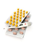 Tabuletas para o tratamento da doença e do termômetro no branco Fotografia de Stock Royalty Free