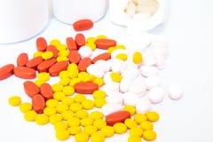Tabuletas vermelhas, amarelas, cor-de-rosa e garrafas brancas da medicina fotografia de stock royalty free