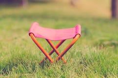 Taburete que acampa plegable en el parque al aire libre Fotos de archivo libres de regalías