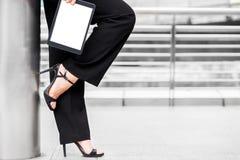 Tacón alto del desgaste de la mujer de negocios y tableta del control foto de archivo libre de regalías