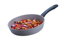 Tacchino delizioso dell'arrosto con i peperoni e le cipolle in una padella con una maniglia nera su un fondo bianco Fotografie Stock Libere da Diritti