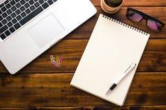 Taccuini bianchi e computer portatile che mettono su una tavola di legno Fotografia Stock
